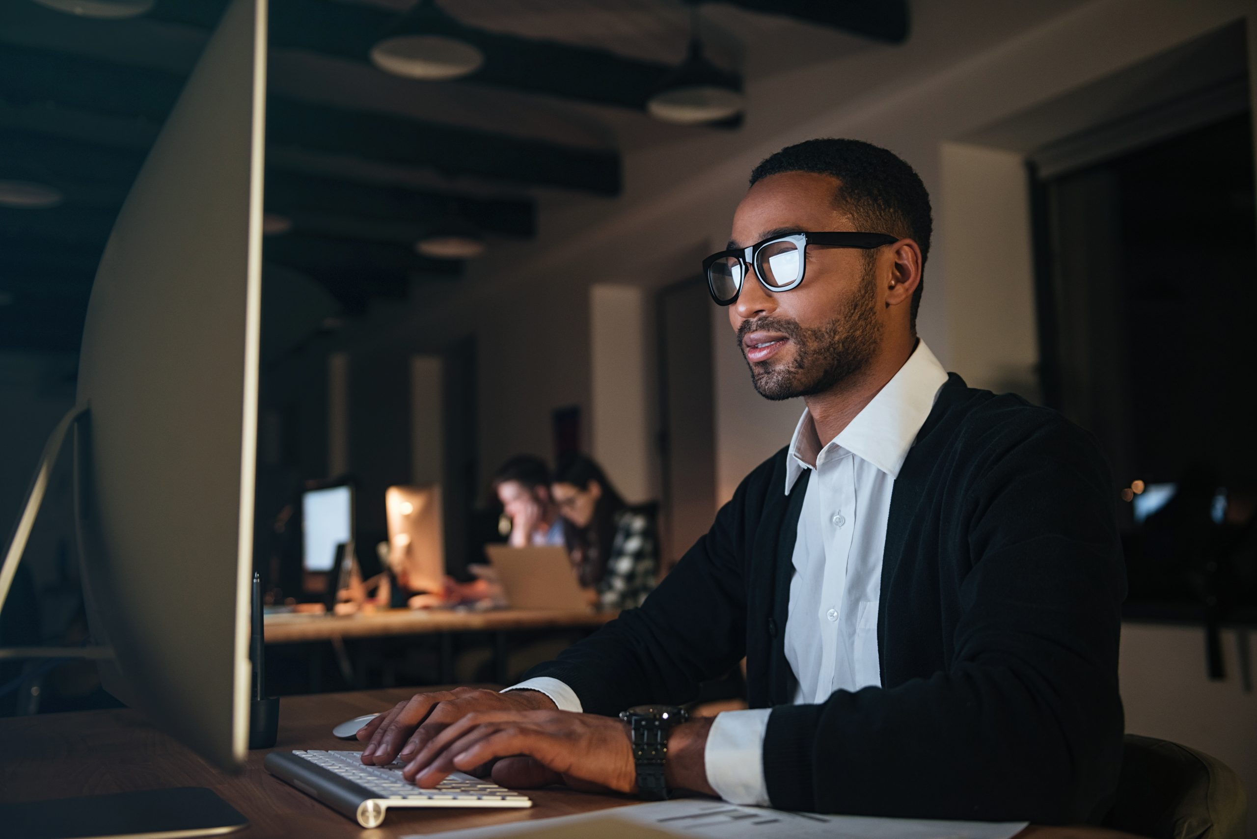 Concentrated dark skinned businessman working late at night in office with computer.